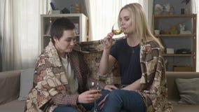 Dos jovenes, las muchachas hermosas se están sentando en el sofá que envuelve con la manta caliente de la tela escocesa, el vino  almacen de video