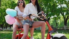 Dos jovenes y los amigos morenos atractivos con el pelo flojo en dril de algodón corto pone en cortocircuito montar una motocicle metrajes