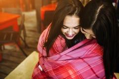 Dos jovenes y muchachas hermosas que se divierten en café Imagen de archivo libre de regalías