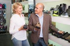 Dos jubilados juntos que eligen pares de zapatos para los hombres en sto del zapato Foto de archivo libre de regalías