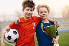 Dos jugadores de fútbol felices de los muchachos que celebran el balón de fútbol y el trofeo de oro imagenes de archivo