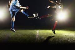 Dos jugadores de fútbol que golpean un balón de fútbol con el pie en el juego Imagen de archivo
