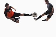 Dos jugadores de fútbol que golpean un balón de fútbol con el pie Imágenes de archivo libres de regalías
