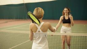 Dos jugadores de tenis de sexo femenino competentes cheerfuly se saludan, sacuden las manos en el área cubierta del campo de teni almacen de video