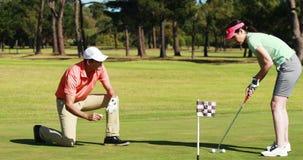 Dos jugadores del golfista que juegan al golf junto almacen de metraje de vídeo