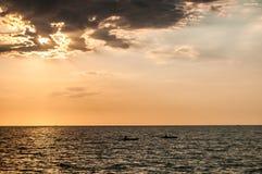 Dos Kayakers Kayak en la puesta del sol Imagen de archivo libre de regalías