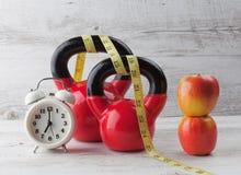 Dos kettlebells rojos con la cinta métrica, las manzanas, y el reloj Imagenes de archivo