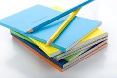 Dos lápices coloreados bajo la pila de libros Fotografía de archivo libre de regalías