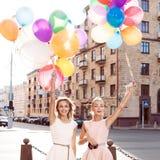 Dos ladys hermosos en el equipo retro que sostiene un manojo de globos Imagen de archivo