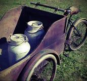 Dos latas viejas de la leche transportadas por un carro viejo Foto de archivo