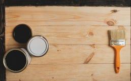 Dos latas y cepillos de la pintura en fondo de madera con la copia espacian en el centro, visión superior Imagenes de archivo