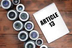 Dos lentes fotográficas y cuadernos con la inscripción del artículo 13 imagen de archivo libre de regalías