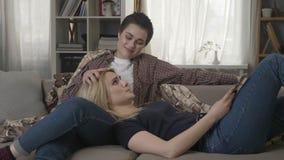 Dos lesbianas están descansando sobre el sofá con una tableta del ordenador portátil, problemas con uno a, confianza de la parte  almacen de video