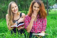 Dos libros de lectura de los adolescentes en parque Imagen de archivo libre de regalías