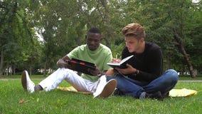 Dos libros de lectura jovenes de los estudiantes en la escuela metrajes