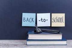 Dos libros, en los cuales está un marcador y una abrazadera y los trozos de papel con la inscripción de nuevo a escuela Imagen de archivo