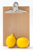Dos limones delante de la tabla de madera del boletín imagen de archivo libre de regalías