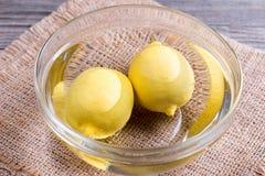 Dos limones en un cuenco de agua Fotografía de archivo