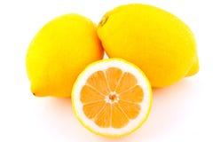 Dos limones enteros y medio limón Imágenes de archivo libres de regalías