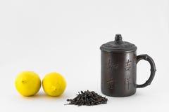 Dos limones, taza china y té seco en el fondo blanco Imágenes de archivo libres de regalías