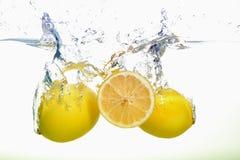 Dos limones y spash amarillos de la rebanada del limón en agua en el fondo blanco fotos de archivo libres de regalías