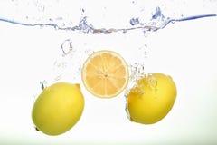 Dos limones y spash de la rebanada del limón en agua en el fondo blanco imagen de archivo libre de regalías