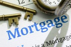 Dos llaves de cobre amarillo del vintage y un reloj de bolsillo en un manual fundamental de la instrucción de la hipoteca imágenes de archivo libres de regalías