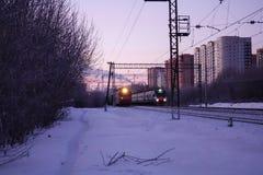 Dos locomotoras son curso paralelo Carga y tren de pasajeros que se mueven a Moscú Rusia El sol se levanta sobre las nubes del ma fotos de archivo libres de regalías