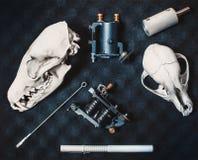 Dos máquinas para los tatuajes con una aguja y piezas, mentira gris del dibujo del marcador en el primer negro del tiro del paral Imagen de archivo libre de regalías