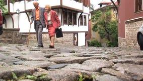 Dos más viejas personas que caminan abajo de la calle en Plovdiv, Bulgaria almacen de video