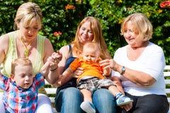 Dos madres con la abuela y los niños en parque Imagen de archivo