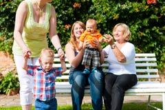 Dos madres con la abuela y los niños en parque Foto de archivo libre de regalías