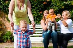 Dos madres con la abuela y los niños en parque Foto de archivo