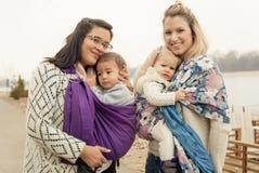 Dos madres con los bebés en la deformación de los portadores de bebé Imagenes de archivo