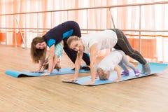 Dos madres jovenes con sus niños hacen la gimnasia imagenes de archivo
