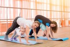 Dos madres jovenes con sus niños hacen la gimnasia fotos de archivo libres de regalías