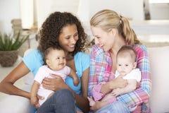 Dos madres jovenes en Sofa At Home Foto de archivo
