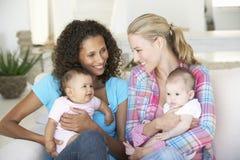 Dos madres jovenes en Sofa At Home Foto de archivo libre de regalías