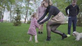 Dos madres lindas que juegan con ellos a niños en parque asombroso verde en la naturaleza el día de primavera Mamá e hijo, hija q almacen de video