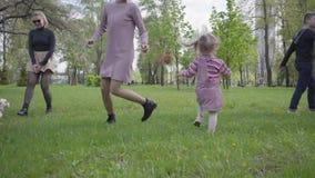 Dos madres lindas que juegan con ellos a ni?os en parque asombroso verde en la naturaleza el d?a de primavera Mam? e hijo, hija q almacen de video