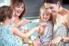 Dos madres y sus hijas que cuecen una torta foto de archivo libre de regalías