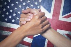 Dos manos con la bandera de Inglaterra y de Estados Unidos Imagenes de archivo