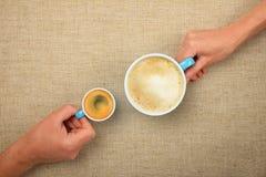 Dos manos con las tazas de café del capuchino del café express Imagen de archivo libre de regalías