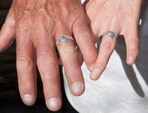 Dos manos con los anillos de bodas Fotos de archivo libres de regalías