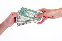 Dos manos con los dólares del dinero Foto de archivo