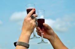 Dos manos con los vidrios de vino rojo Fotografía de archivo libre de regalías