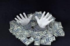 Dos manos de cerámica blancas con las esposas en la pila de 100 notas del dólar Foto de archivo