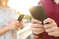 Dos manos de la muchacha usando los teléfonos elegantes Imagenes de archivo