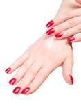 Dos manos de la mujer con crema corporal Foto de archivo libre de regalías