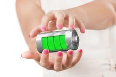 Dos manos de la mujer que protegen la batería de carga abstracta con la carga Fotos de archivo